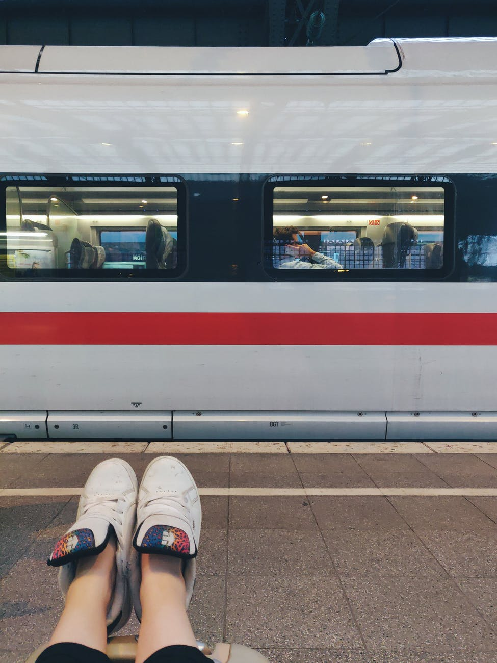 photo of person sitting on floor near train